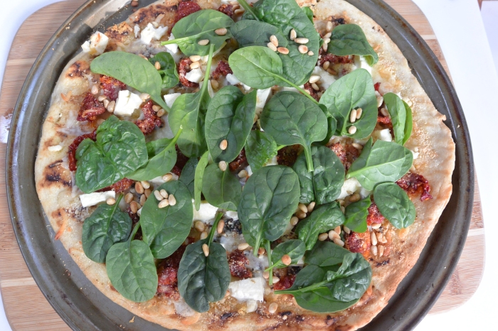 top with spinach and pine nuts